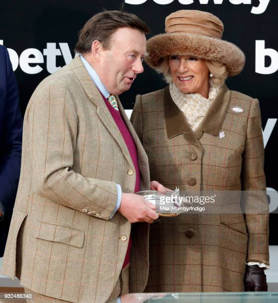 Camilla Duchess of Cornwall presents Nicky Henderson with the winning trainer prize after 'Altior' won the Queen Mother Champion Chase on day 2...