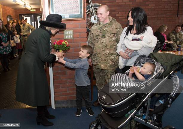 Camilla Duchess of Cornwall receives flowers from Zac Darker as she visits the 4th Battalion The Rifles at Normandy Barracks on February 27 2017 in...