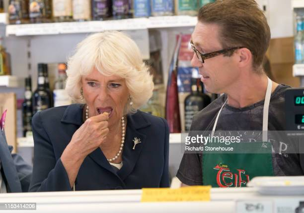 Camilla Duchess of Cornwall samples cheese as she visits a cheese stall at Carmarthen Market where she met various stallholders during a visit to...