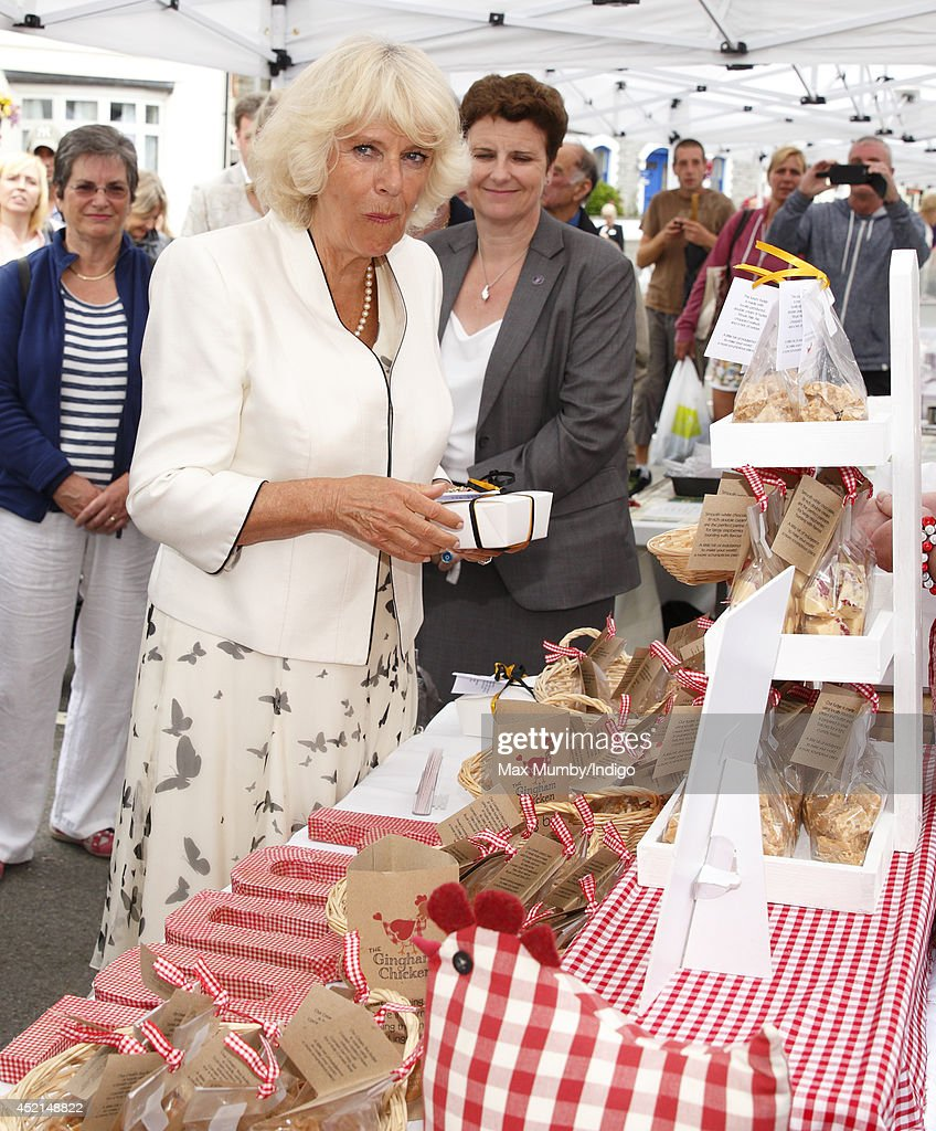 Camilla, Duchess of Cornwall samples some fudge as she and Prince Charles, Prince of Wales tour a market on day one of their annual visit to Devon and Cornwall on July 14, 2014 in Looe, England.