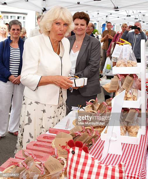 Camilla Duchess of Cornwall samples some fudge as she and Prince Charles Prince of Wales tour a market on day one of their annual visit to Devon and...