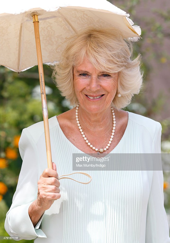 Camilla, Duchess of Cornwall shelters under a parasol as she attends The Hampton Court Flower Show at Hampton Court Palace on July 1, 2015 in London, England.