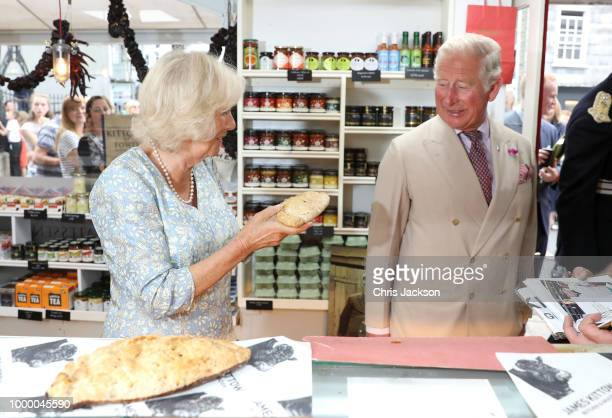 Camilla Duchess Of Cornwall shows Prince Charles Prince Of Wales a Cornish Pasty as they tour local businesses during the Fowey Festival Celebration...
