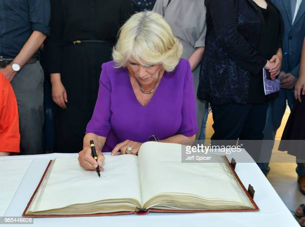 Camilla Duchess of Cornwall signs the Roll book with T S Elliot's pen at The Royal Society of Literature '40 Under 40' fellow induction at The...
