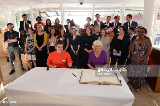 Camilla Duchess of Cornwall signs the Roll book with T S Elliot's pen infront of the new fellows and Molly Rosenberg Director of Royal Society of...
