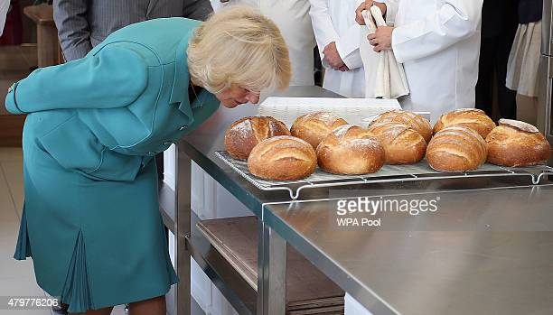 Camilla Duchess of Cornwall smells freshly baked bread during her tour of the Village Bakery on July 7 2015 in Wrexham Wales United Kingdom