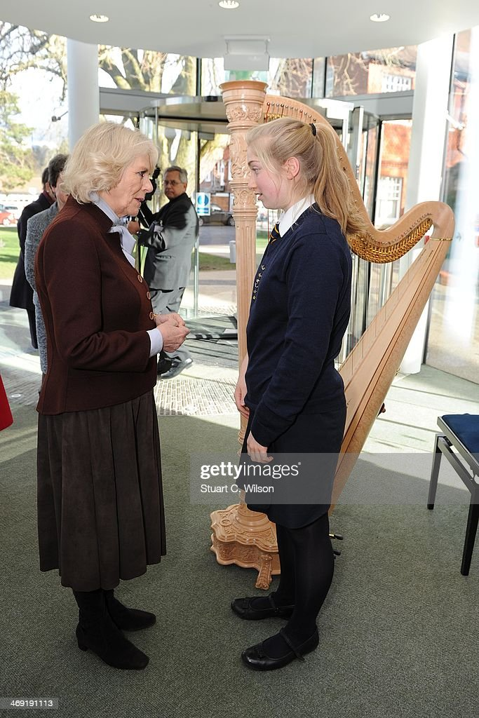 Camilla, Duchess Of Cornwall speaks to a young girl near a harp as she visits St Catherine's School in Bramley, Surrey on February 13, 2014 in Guildford, England.