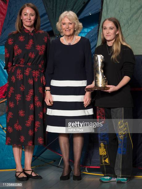 Camilla Duchess Of Cornwall stands with Caroline Rush Chief Executive of The British fashion Council and designer Bethany Williams who was awarded...