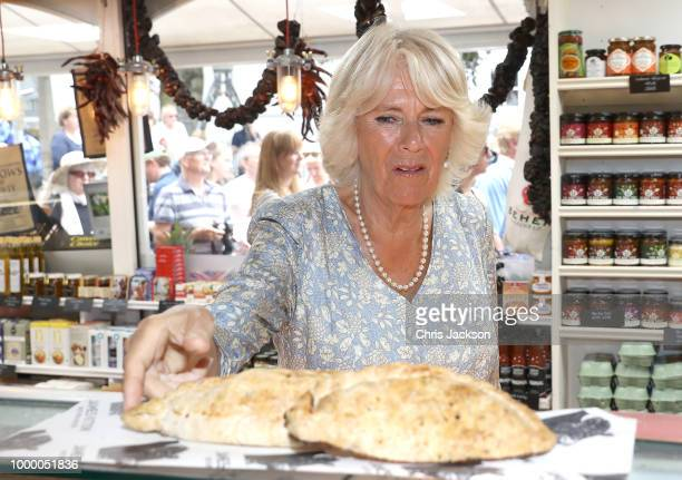 Camilla Duchess Of Cornwall takes a Cornish Pasty as she tours local businesses with Prince Charles Prince Of Wales during the Fowey Festival...