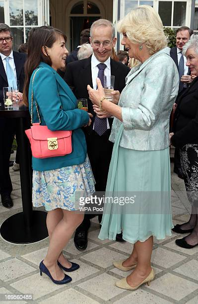 Camilla Duchess of Cornwall talks with food writer and blogger Rachel Khoo as she attends a reception at the British Embassy on May 27 2013 in Paris...