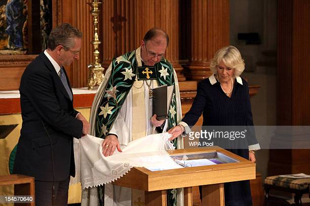 Camilla Duchess of Cornwall unveils a memorial page to Marie Colvin with the Rector David Meara and John Witherow the Sunday Times Editor as she...