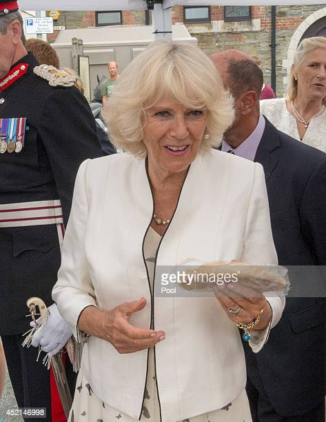 Camilla, Duchess of Cornwall visits Looe Market and buys some Cornish pasty on July 14, 2014 in Looe, England.