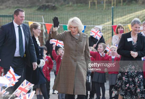 Camilla Duchess of Cornwall waves goodbye to flag waving school pupils as she leaves following a visit to Marlborough St Mary's Church of England...