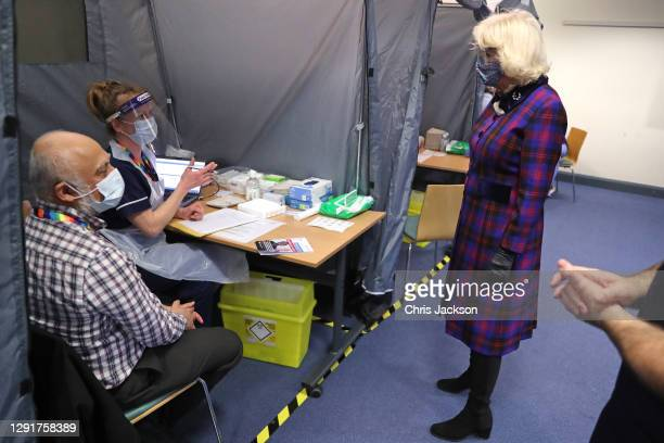 Camilla, Duchess of Cornwall wears a face-mask and protective glasses while speaking with front line health and care workers administering and...