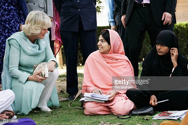 Camilla Duchess of Cornwall wears a traditional shalwar kameez in turquoise to meet students at the all female Fatima Jinnah University on October 31...