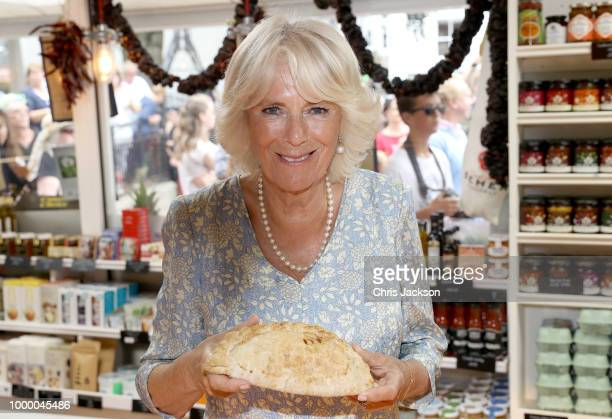 Camilla Duchess Of Cornwall with a Cornish Pasty as she tours local businesses with Prince Charles Prince Of Wales during the Fowey Festival...