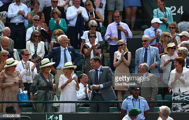 Camilla Duchess of Cornwall with AELTC Chairman Philip Brook holds the wrist band that Andy Murray threw into the crowd on Centre Court during day...