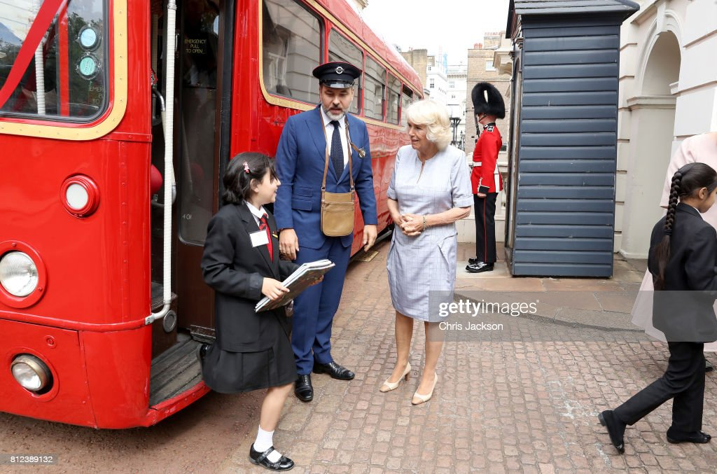 Camilla, Duchess of Cornwall with comedian and author David Walliams, dressed as an bus conductor, as school children from Hemlington Hall Academy in Middlesbrough and Berkeley Primary School in Hounslow disembark a bus ahead of a tea party hosted by the Duchess of Cornwall to celebrate the Duchess's Bookshelves Project at Clarence House on July 11, 2017 in London, England. The Project is an initiative to find the nation's 70 favourite children's books to mark the Duchess of Cornwall's 70th birthday.