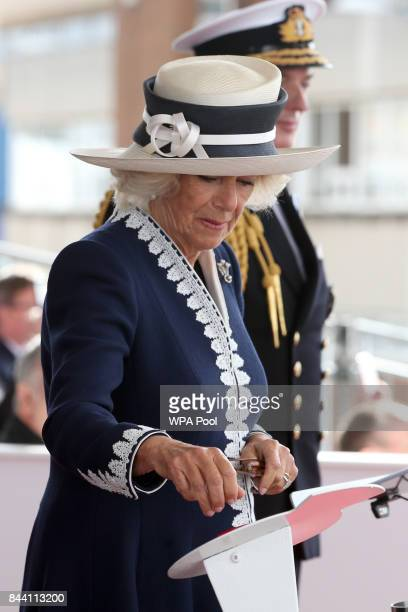 Camilla Duchess of Rothesay presses the button to release a bottle of whisky during a naming ceremony of aircraft carrier HMS Prince of Wales at the...