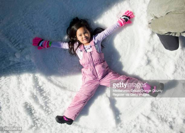 Camilla Li of Rowland Heights makes a snow angel during the Discovery Cube's second annual Winter Wonderfest in Santa Ana on Saturday December 17 2016