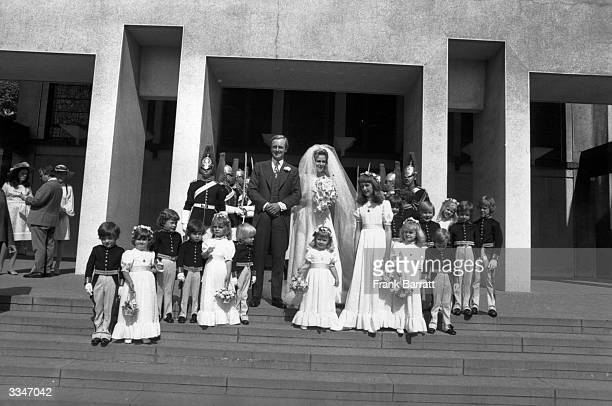 Camilla Shand and Captain Andrew Parker Bowles on the steps of the Guards' Chapel on their wedding day amongst bridesmaids pages and men of the Guard...