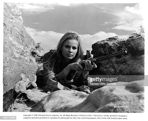 Camilla Sparv holding large gun in between the rocks in a scene from the film 'Mackenna's Gold' 1969