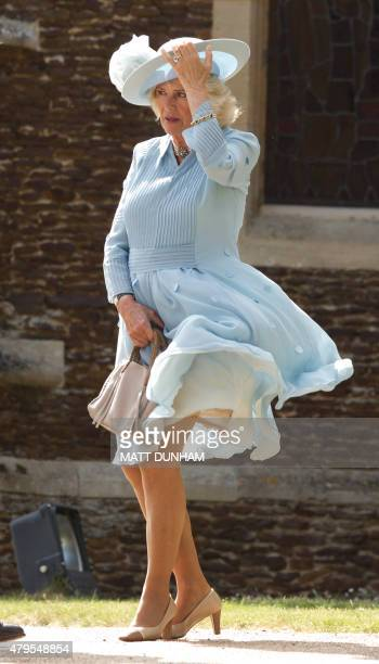 Camilla, The Duchess of Cornwall battles with the wind as she attends Princess Charlotte of Cambridge's Christening at St. Mary Magdalene Church in...
