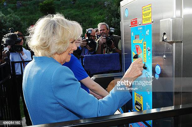 Camilla the Duchess of Cornwall during her visit to the Wellington SPCA puts a coin in the machine for the dog wash area on November 7 2015 in...