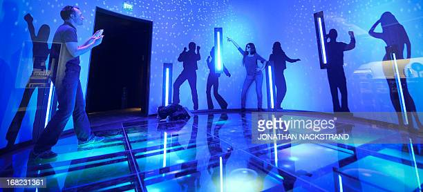 Camille BASWOHLERT A visitor poses next to silhouettes featuring the members of Swedish disco band ABBA on May 7 2013 in Stockholm at world's first...