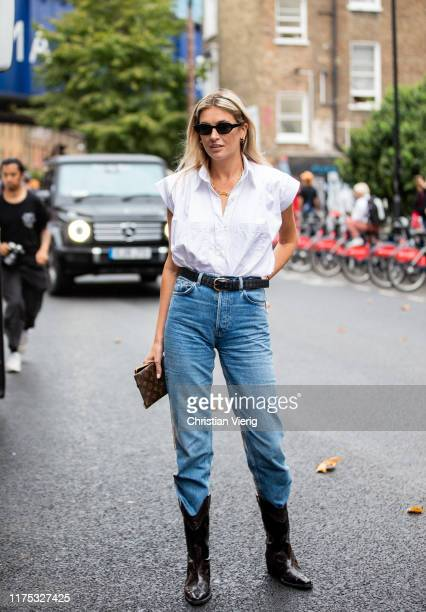 Camille Carriere is seen wearing denim jeans, white sleeveless button shirt, cowboy boots outside Christopher Kane during London Fashion Week...