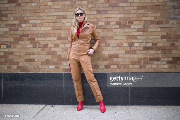 Camille Charierre is seen on the street attending Ralph Lauren during New York Fashion Week wearing a tan leather jumpsuit with red sweater and red...