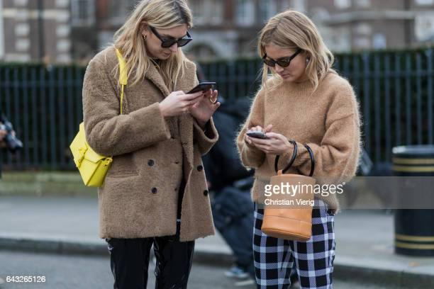 Camille Charriere and Lucy Williams wearing a beige knit bucket bag checked pants silver ankle boots outside Christopher Kane on day 4 of the London...