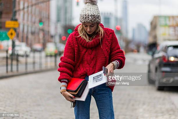 Camille Charriere is wearing a creme Mischa Lampert knit cap and a red heavy knitted jumper and blue denim jeans seen outside Delpozo during New York...