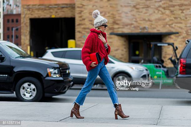 Camille Charriere is wearing a creme Mischa Lampert knit cap and a red heavy knitted jumper and blue denim jeans seen outside Boss during New York...