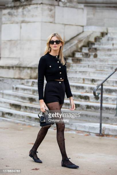 Camille Charriere seen wearing sheer tights, black shorts and jacket, mini bag outside Chanel during Paris Fashion Week - Womenswear Spring Summer...