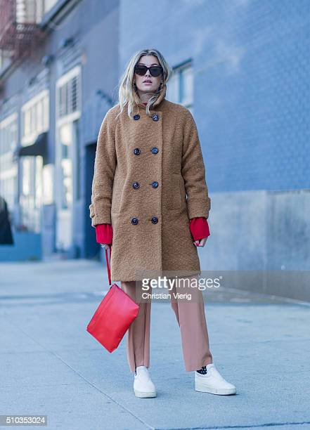 Camille Charriere wearing a brown Ganni fake fur coat a red Topshop sweater a red Claritone bag Tibi pants seen outside Lacoste during New York...