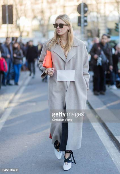 Camille Charriere wearing a grey coat Loewe clutch outside Jil Sander during Milan Fashion Week Fall/Winter 2017/18 on February 25 2017 in Milan Italy