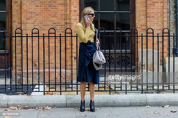 Camille Charriere wearing a yellow jumper and navy skirt outside Anya Hindmarch during London Fashion Week Spring/Summer collections 2017 on...