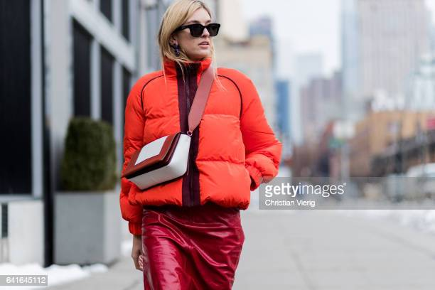 Camille Charriere wearing an orange down feather jacket red pvc skirt Converse sneaker outside Creatures of the Wind on February 11 2017 in New York...