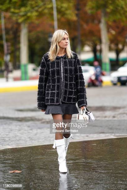 Camille Charriere wears a black and gray checked tweed jacket, a gray skirt, a white bag, tights, white boots, outside Chanel, during Paris Fashion...