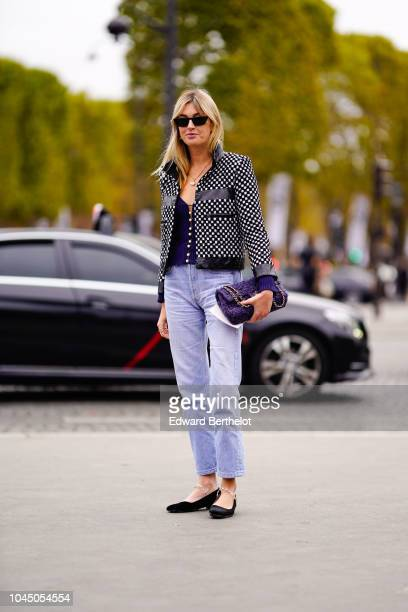 Camille Charriere wears a black and white checked print jacket a blue Chanel bag blue jeans outside Chanel during Paris Fashion Week Womenswear...