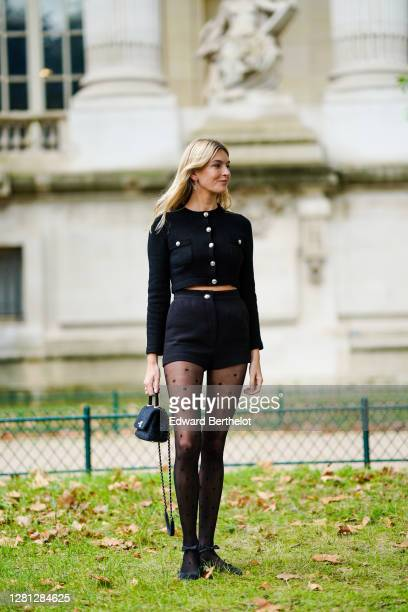 Camille Charriere wears a black cardigan with buttons, black shorts, Chanel logo earrings, tights with printed polka dots, a Chanel bag, outside...