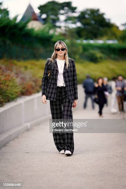 Camille Charriere wears a black checked blazer jacket suit pants outside Dior during Paris Fashion Week Womenswear Spring/Summer 2019 on September 24...