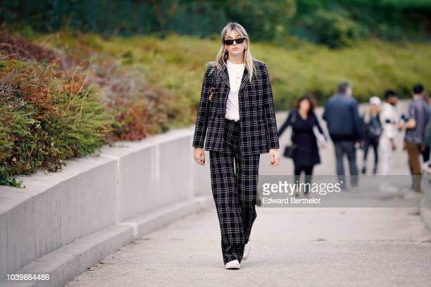 Camille Charriere wears a black checked blazer jacket, suit pants, outside Dior, during Paris Fashion Week Womenswear Spring/Summer 2019, on...