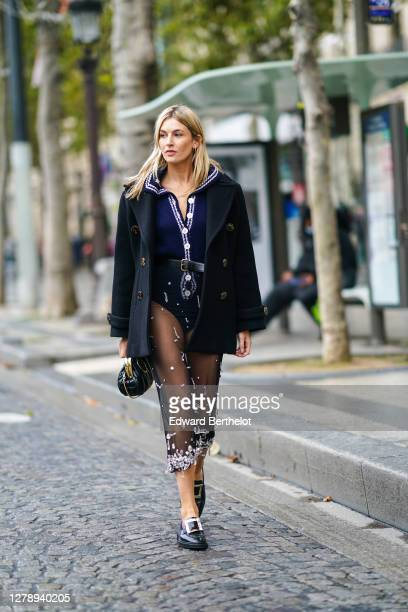 Camille Charriere wears a black coat, a blue wool body suit with white embroidery and buttons, a leather belt, a black mesh skirt, black leather...