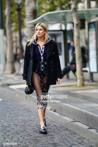 Camille Charriere wears a black coat a blue wool body suit with white embroidery and buttons a leather belt a black mesh skirt black leather shoes...