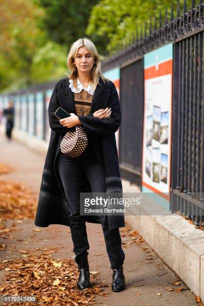 Camille Charriere wears a black coat, a brown wool pullover with printed patterns, a shirt with ruffled collar, a bag with checked printed patterns,...
