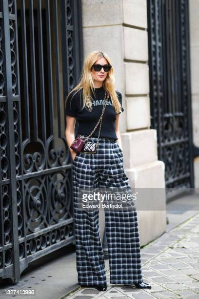 Camille Charriere wears a black ribbed with white Chanel rhinestones logo crop-top from Chanel, black sunglasses, silver Chanel earrings, a burgundy...
