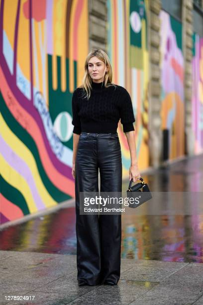 Camille Charriere wears a black turtleneck pullover, black leather flared pants, a Vuitton bag, outside Louis Vuitton, during Paris Fashion Week -...
