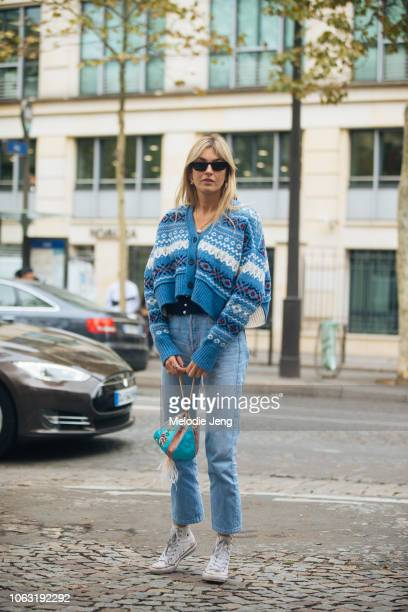 Camille Charriere wears a blue patterned knit cardigan blue jeans an oriental style bag and white Converse sneakers before the Miu Miu show during...